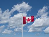 picture of canada maple leaf  - The red and white maple leaf flag of Canada flies from a white flagpole against a blue sky filled with large fluffy white clouds - JPG