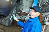 picture of auto garage  - portrait of car mechanic worker before repairing suspension of lifted automobile at auto repair garage shop station - JPG