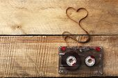 picture of heart sounds  - Audio cassette with magnetic tape in shape of heart on wooden background - JPG