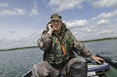 image of life-boat  - man dressed in a life jacket operates a motor boat - JPG