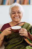picture of sari  - Portrait of senior Indian woman in sari drinking tea - JPG