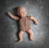 picture of forlorn  - Abandoned doll laying on a concrete floor - JPG