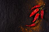 image of chili peppers  - Chili peppers on black stone with chili powder - JPG