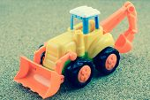 image of backhoe  - Vintage Style Tractor Backhoe Toy on sand - JPG