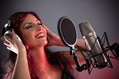 image of singer  - Young singer screaming on the studio microphone - JPG