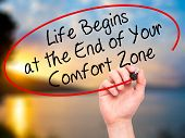 Постер, плакат: Man Hand writing Life Begins at the End of Your Comfort Zone with black marker on visual screen