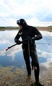 stock photo of hunter  - Underwater hunter in a wetsuit in the lake - JPG