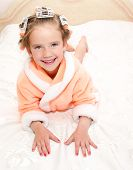picture of hair curlers  - Happy funny little girl with manicure and hair curlers in bathrobe lying on bed - JPG