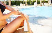 foto of woman bikini  - Woman applying sun cream - JPG