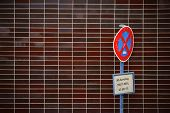 picture of striking  - An old and battered stop sign stands in front of a striking brick facade - JPG