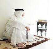 stock photo of arab man  - Arabic aged man sitting on ground using traditional beads - JPG