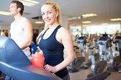 picture of treadmill  - Attractive Fit Young Woman Smiling at the Camera While Exercising on Treadmill Device Inside the Fitness Gym - JPG
