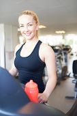 stock photo of treadmill  - Close up Cheerful Fit Young Woman in Black Sleeveless Shirt Exercising on Treadmill Machine Inside the Gym Smiling at the Camera - JPG