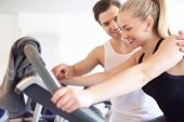 foto of elliptical  - Sweet Athletic Handsome Boyfriend Assisting his Pretty Girlfriend Doing an Exercise on Elliptical Bike Inside the Gym - JPG