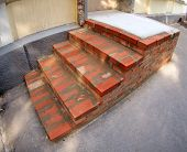 image of distortion  - The steps of the porch outside the house of red brick under construction with wide angle distortion view - JPG