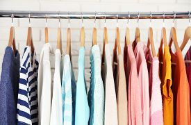 stock photo of department store  - Different clothes on hangers close up - JPG