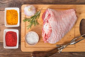 image of turkey-hen  - Raw turkey thigh with spices on a wooden background - JPG