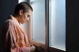 foto of hospital gown  - Young cancer patient standing in front of hospital window - JPG