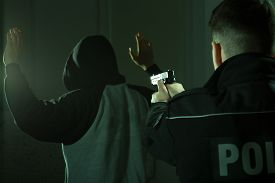 picture of police  - Image of a police officer keeping gun on a crook - JPG
