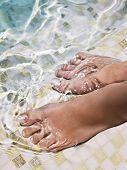 Pies de la mujer en el agua en la piscina