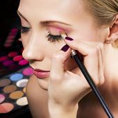 stock photo of makeup artist  - Makeup artist applying pink eyeshadow - JPG