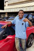 happy man showing key of new red sports car
