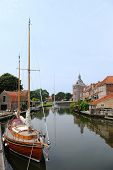 Historic building Dromedaris in Enkhuizen with sailboat