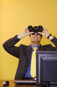 Businessman Looking Up Though Binoculars