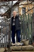 pic of centenarian  - Old man standing in front of his house - JPG