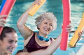 Smiling senior woman doing aqua fitness with swim noodles. Happy mature healthy woman taking fitness poster