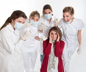 A woman on her knees surrounded by an aggressive group of female dentists