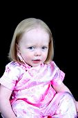 Cute Little Girl Sitting On A Black Background poster