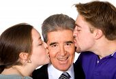 stock photo of full cheeks  - son and daughter kissing their father on the cheek  - JPG
