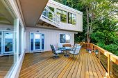 Wooden Walkout Deck With Outdoor Table Set And Swinging Bench poster