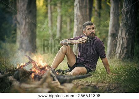 poster of Hipster Hiker With Mug Relax At Bonfire In Forest. Man Traveler Drink Tea At Campfire Flame. Summer
