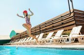 The Portrait Of Happy Smiling Beautiful Teen Girl Jumping At The Swimming Pool. Little Child At Blue poster