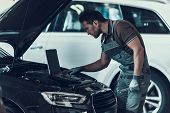 Car Mechanic Working In Auto Repair Shop. Portrait Of Handsome Serious Caucasian Repairman In Grey U poster