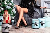 Beautiful woman with long slim legs in sexy black dress posing near the christmas tree poster