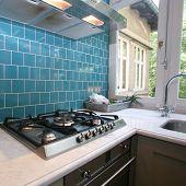 Moderna cocina con azulejos de color turquesas en pared mirando hacia el jardín