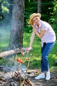 Tips Every Camper Should Know About Campfire Cooking. Girl In Straw Hat Cooking Food At Campfire Nat poster