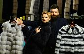 Customer With Beard And Woman Buy Furry Coats. Man And Girl With Serious Faces Hold Furry Coats On C poster