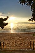 Stairs Leading Down To A Beach With The Sun Setting Over Waskesiu Lake In Prince Albert National Par poster