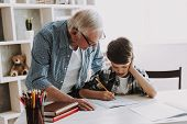 Grandson Doing School Homework With Old Man Home. Family Relationship Between Grandfather And Grands poster