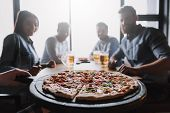 Close Up Of Pizza On Table With Company Friends. Pizza Time. Handsome Company Young Friends Drinking poster
