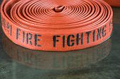 foto of firehose  - A rolled up firehose on the wet floor in a firestation used by firefighters - JPG
