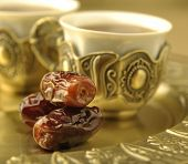 An extreme close up of dates with arabic tea cup