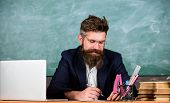 Check Homework. Paperwork Part Of Teachers Life. Teacher Bearded Hipster With Eyeglasses Sit In Clas poster