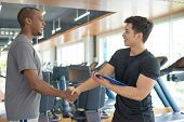 Smiling Black Man Thanking Personal Trainer In Gym. Young Guy Greeting Instructor With Gym Equipment poster