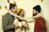 Happy Friends At Autumn Leaves In Scarf And Hat. Girl And Men At Seasonal Brick Wall. Men And Woman, poster