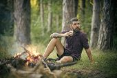Hipster Hiker With Mug Relax At Bonfire In Forest. Man Traveler Drink Tea At Campfire Flame. Summer  poster